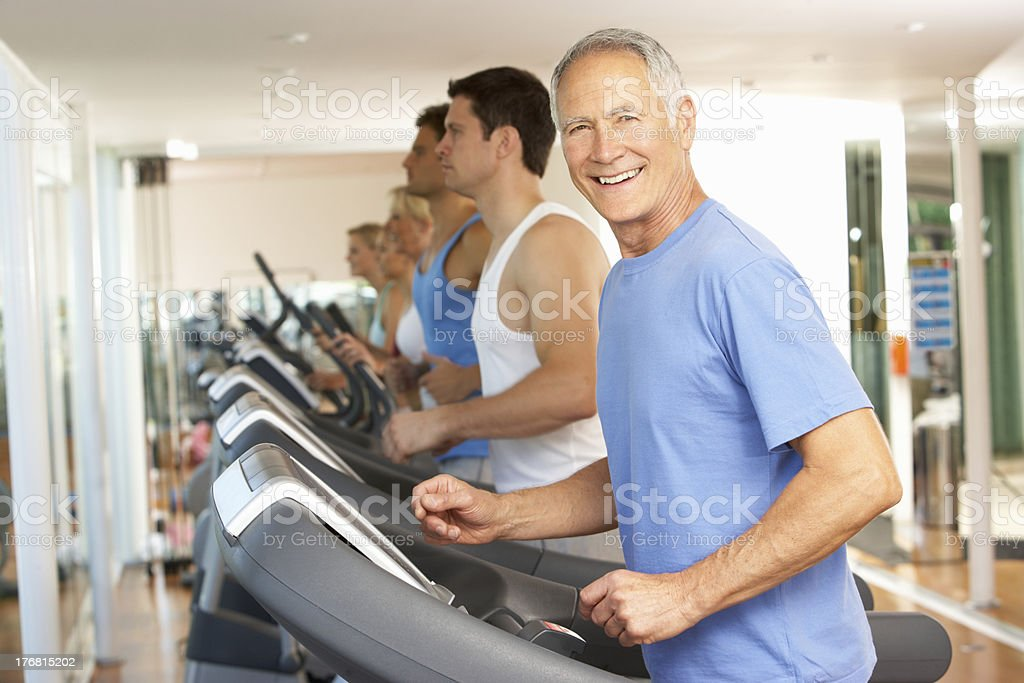 Senior man running on treadmill at gym stock photo