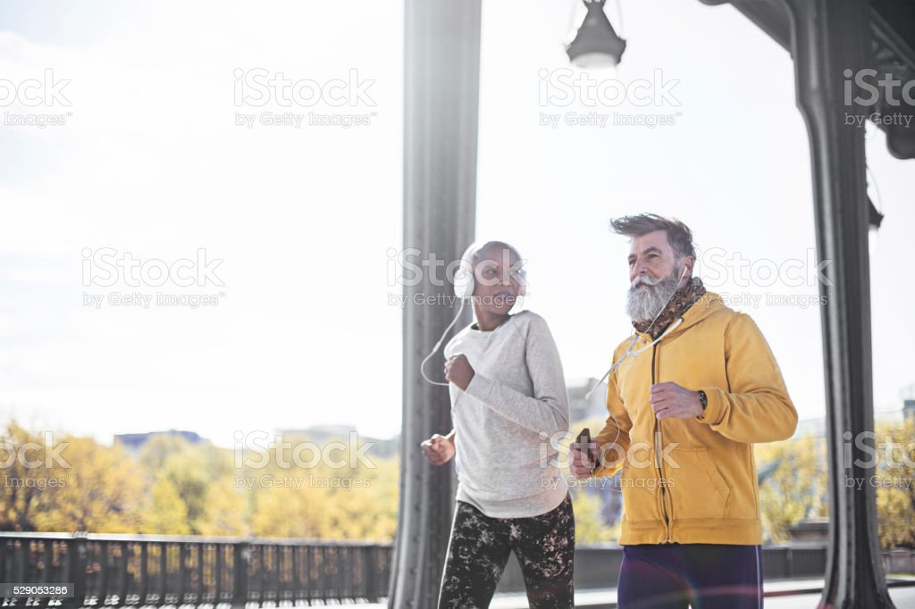 Senior man running with his personal coach in Paris stock photo