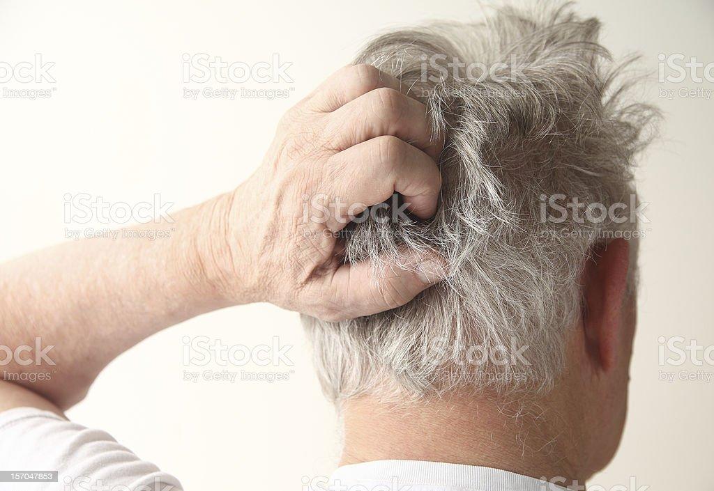 senior man scratching head stock photo