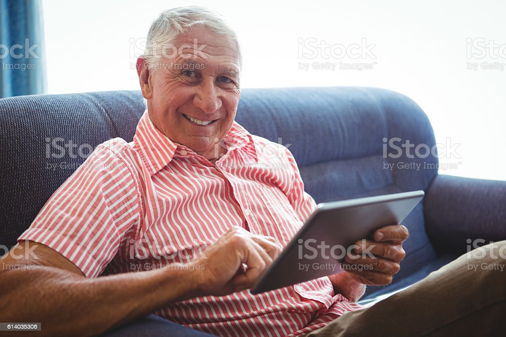 Senior man seated on a sofa looking at camera stock photo