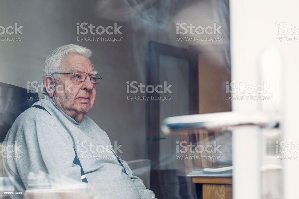 Senior Man Seen Through a Window stock photo