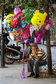 Senior man selling balloons