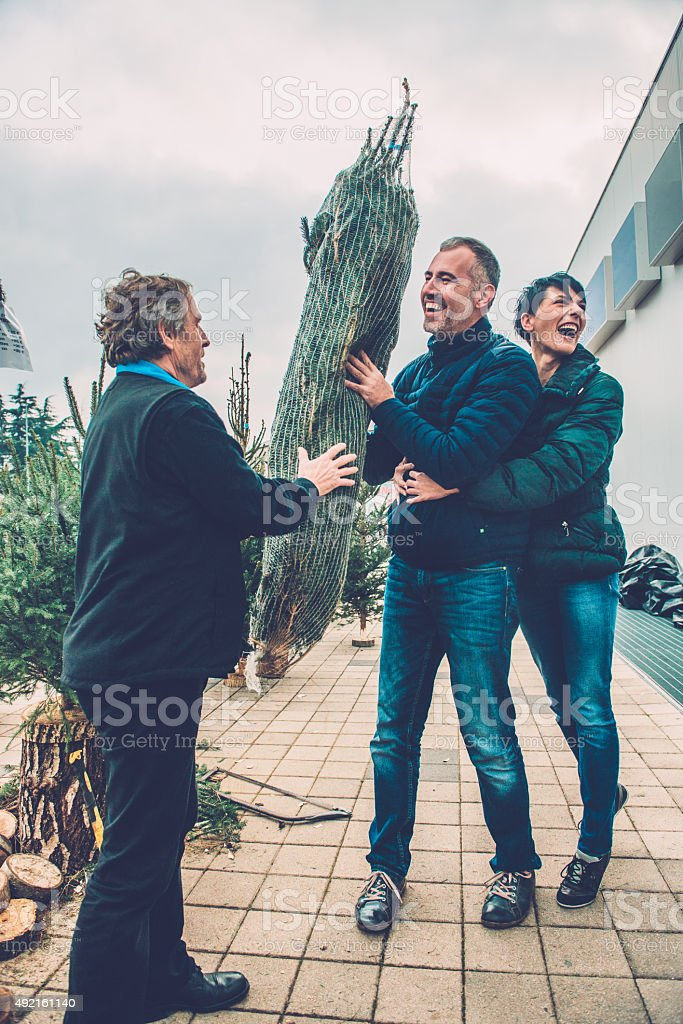 Senior Man Selling Christmas Tree to Happy Couple, Europe stock photo