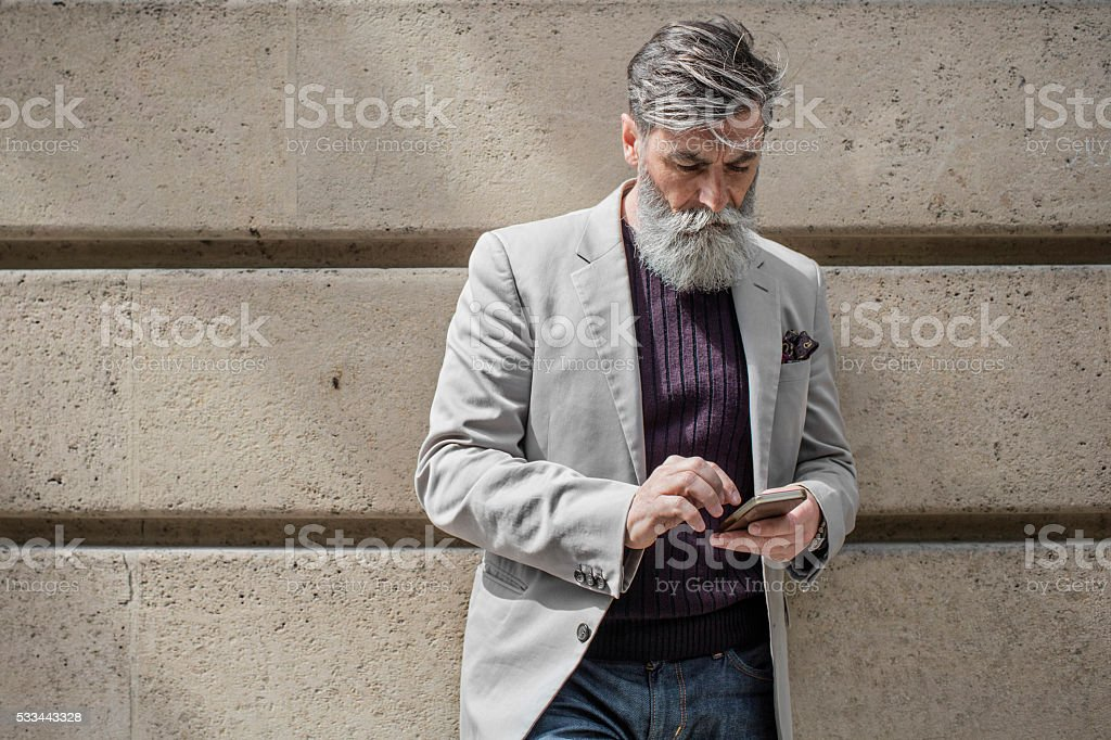 Senior man sending a mobile phone message stock photo