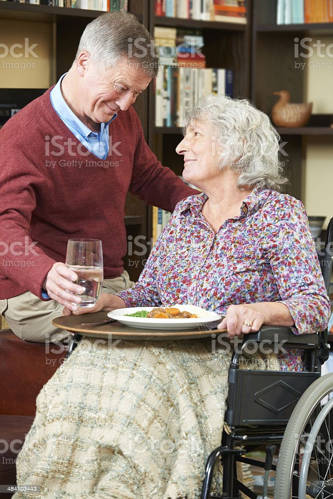 Senior Man Serving Wife In Wheelchair With Meal royalty-free stock photo