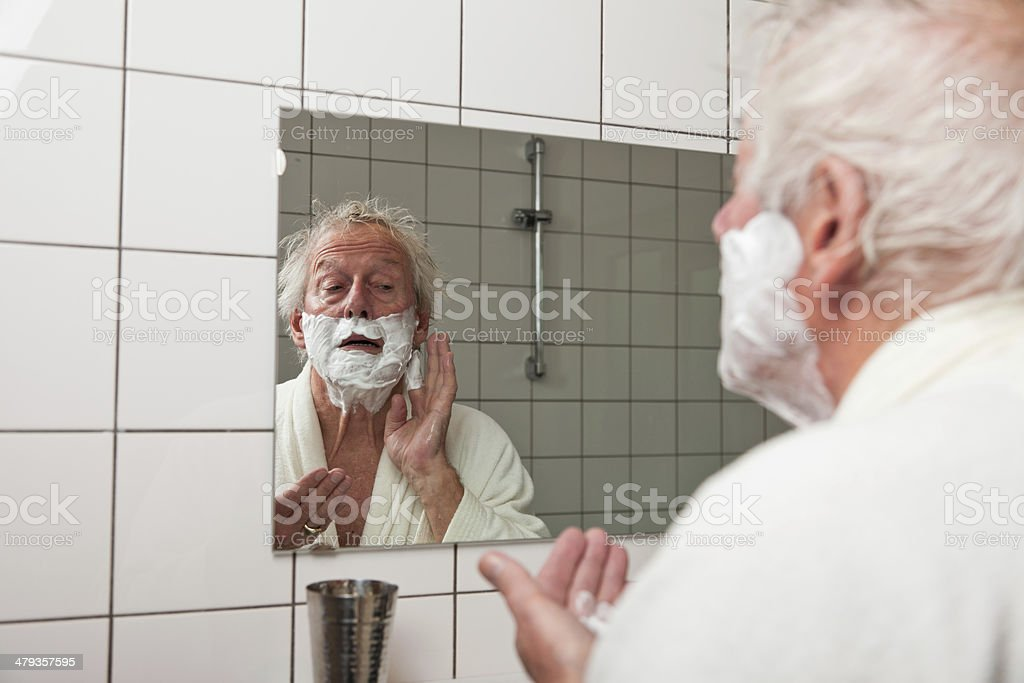 Senior man shaving his beard in bathroom. stock photo