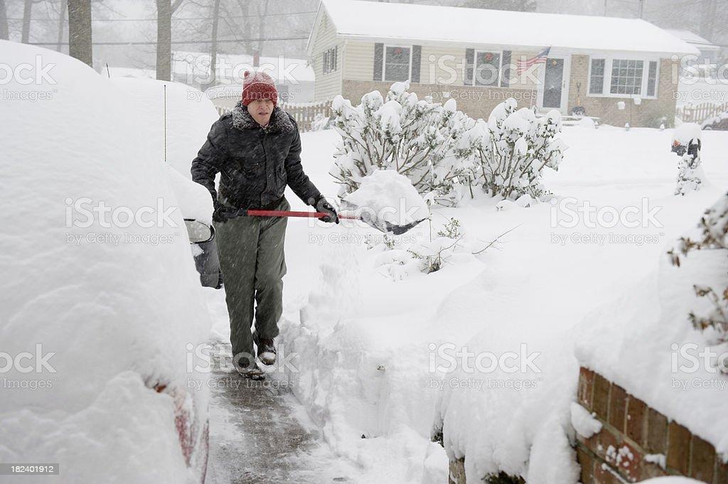 Senior Man Shoveling Snow in Suburbia During Storm royalty-free stock photo