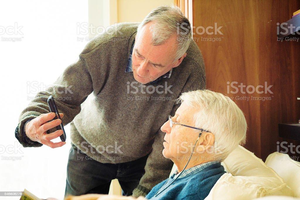 Senior man showing his friend media on mobile phone stock photo