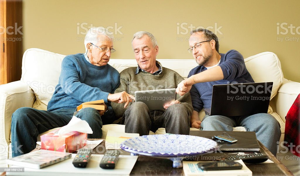 Senior man showing media to friends on tablet stock photo