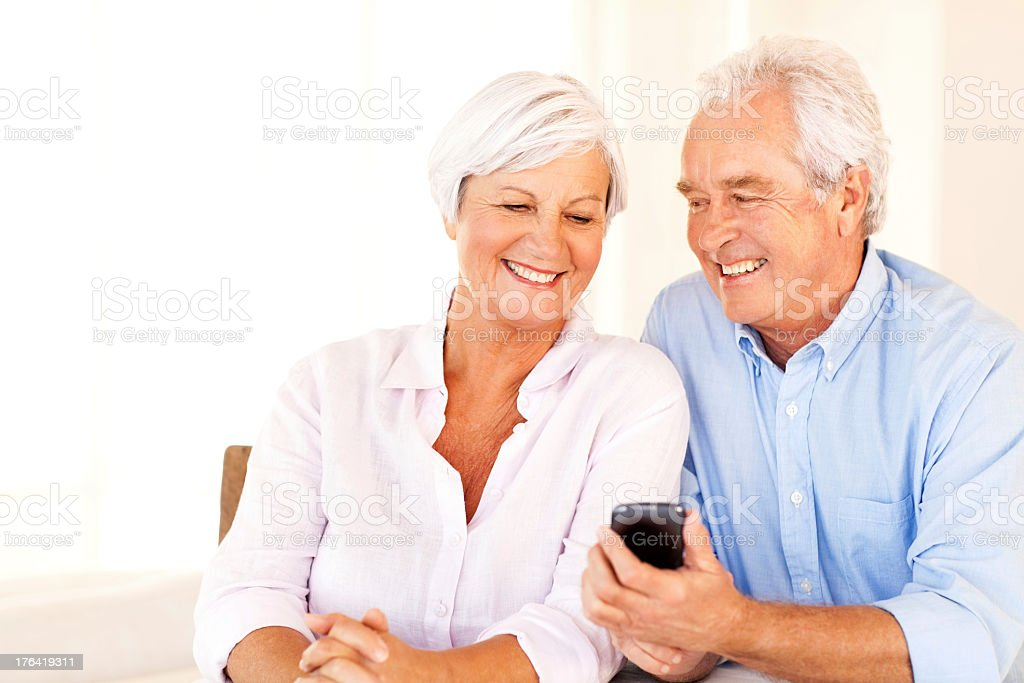 Senior Man Showing Smart Phone To Woman At Home royalty-free stock photo