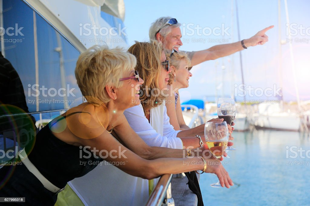 Senior man showing something to their friends on a yacht stock photo