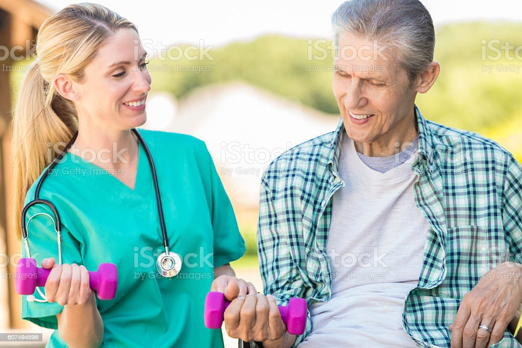 Senior man shows effort in lifting hand weights stock photo