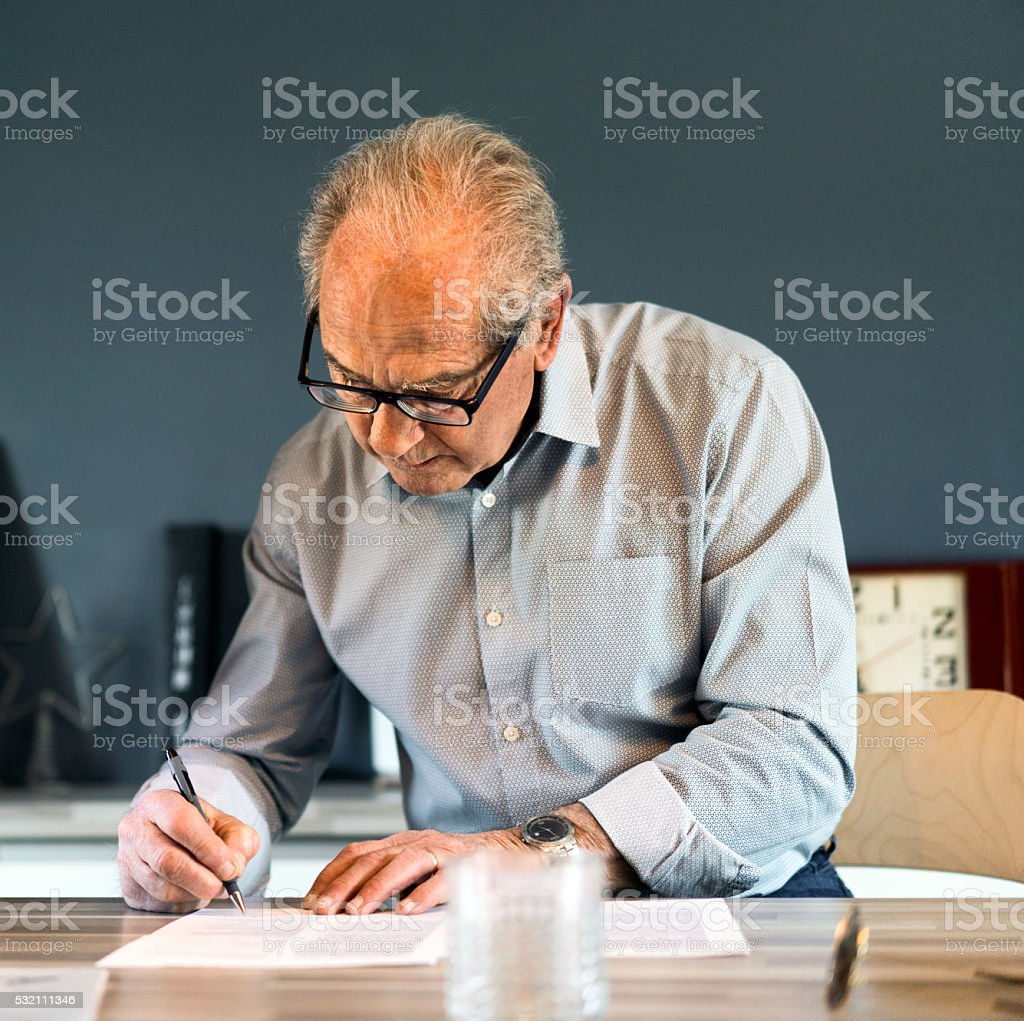 Senior man signing document at table in house stock photo