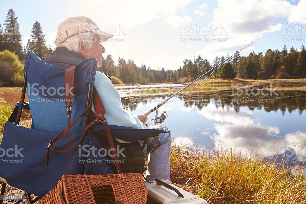 Senior man sits fishing in a lake, back view close-up stock photo