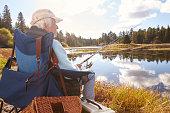 Senior man sits fishing in a lake, back view close-up