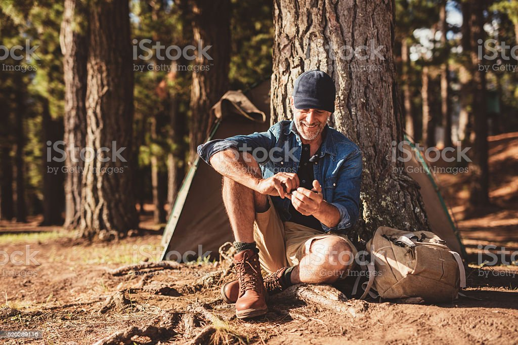Senior man sitting at campsite stock photo