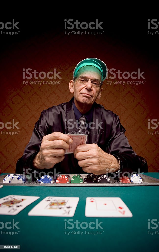 Senior Man Sitting at Card Table and Playing Poker royalty-free stock photo