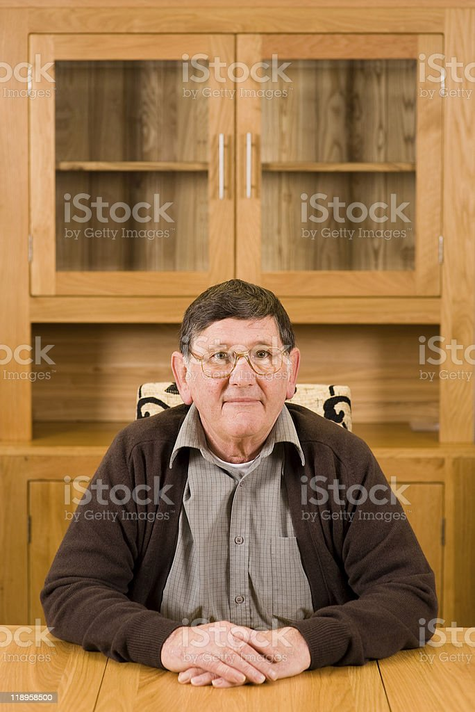 Senior man sitting at table with copyspace above stock photo