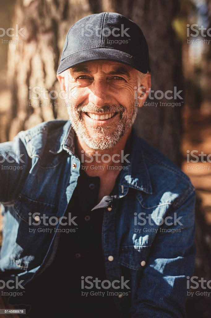 Senior man sitting by a tree on summer day stock photo