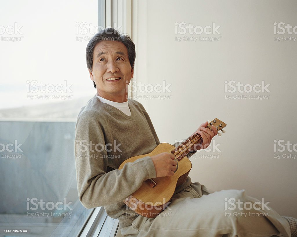 Senior man sitting by window playing ukelele, looking up stock photo