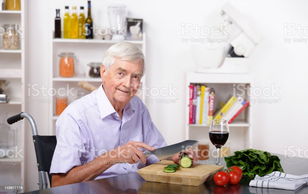 Senior Man Sitting In A Wheelchair And Preparing Healthy Meal stock photo