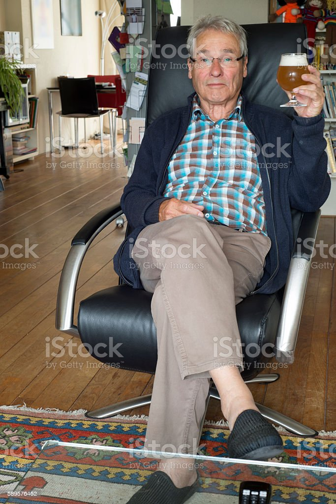 Senior man sitting in armchair reading on his tablet stock photo