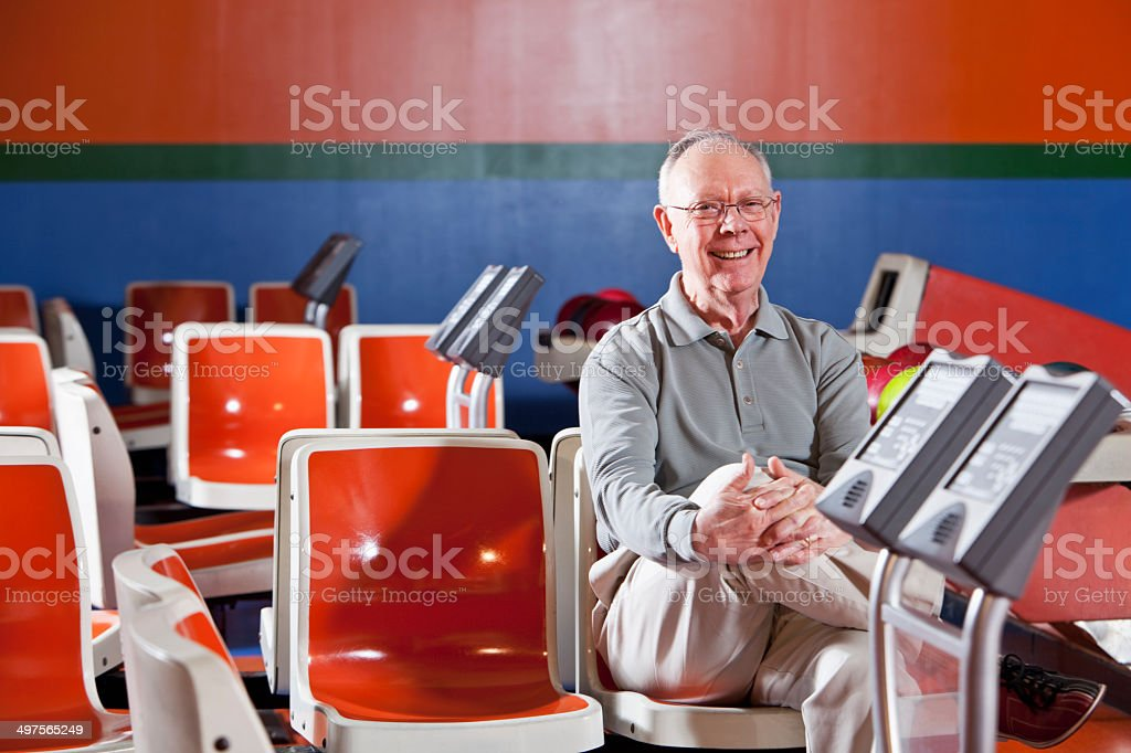 Senior man sitting in bowling alley stock photo