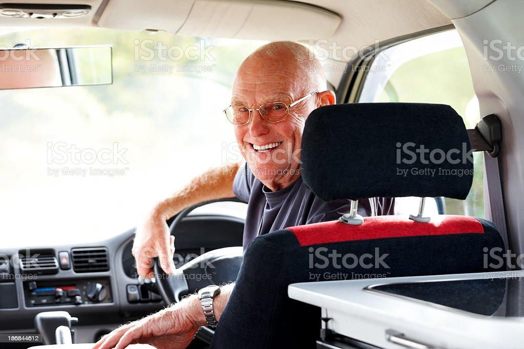 Senior man sitting in his campervan looking happy royalty-free stock photo
