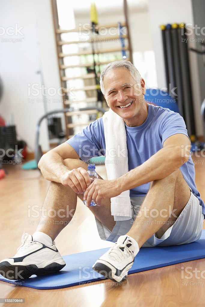 Senior man sitting on a mat and drinking water at a gym royalty-free stock photo