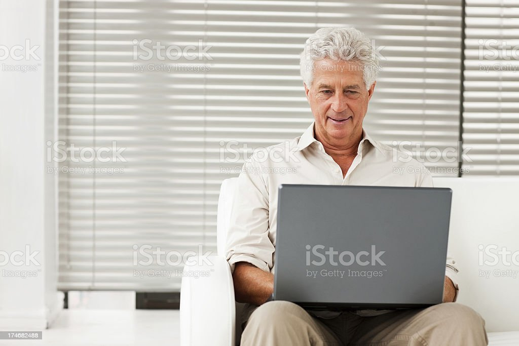 Senior man sitting on a sofa while using laptop royalty-free stock photo