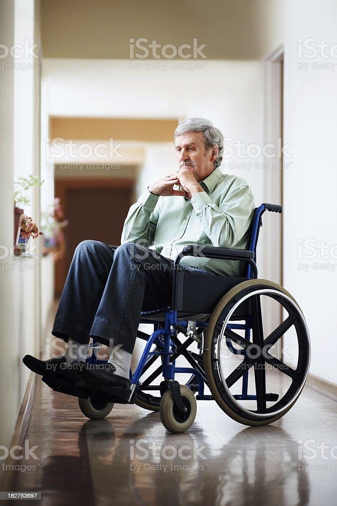 Senior man sitting on a wheelchair at hospital corridor royalty-free stock photo