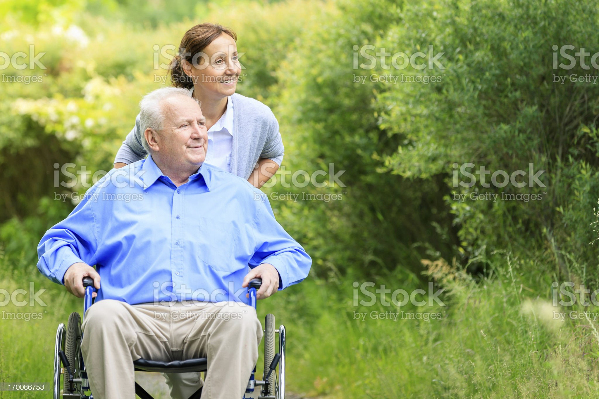 Senior man sitting on a wheelchair with caregiver royalty-free stock photo