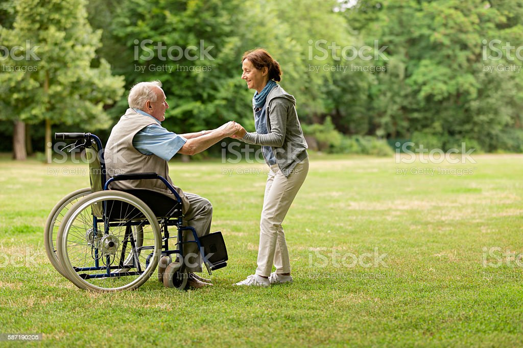 Senior man sitting on a wheelchair with caregiver stock photo