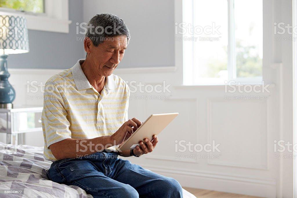 Senior Man Sitting On Bed Using Digital Tablet stock photo