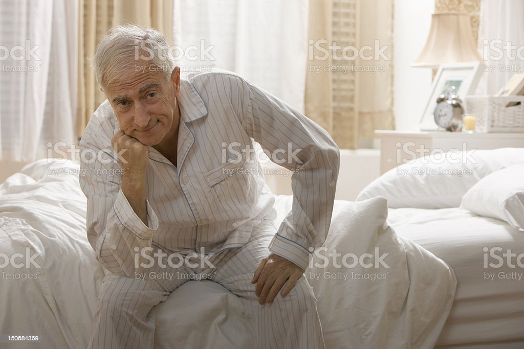 Senior man sitting on bed with hand to chin stock photo
