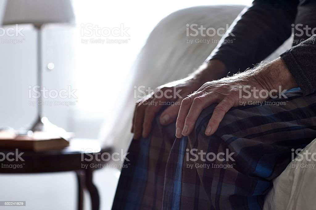 Senior man sitting on bed with his hands on knees stock photo