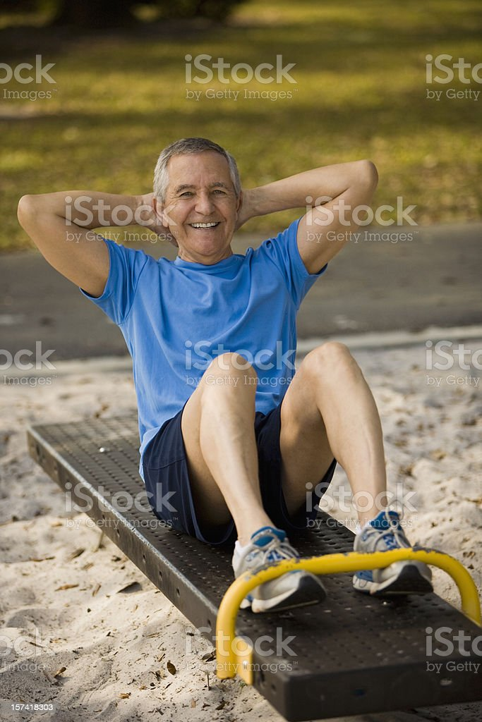 Senior man sitting on bench doing crunches at park royalty-free stock photo