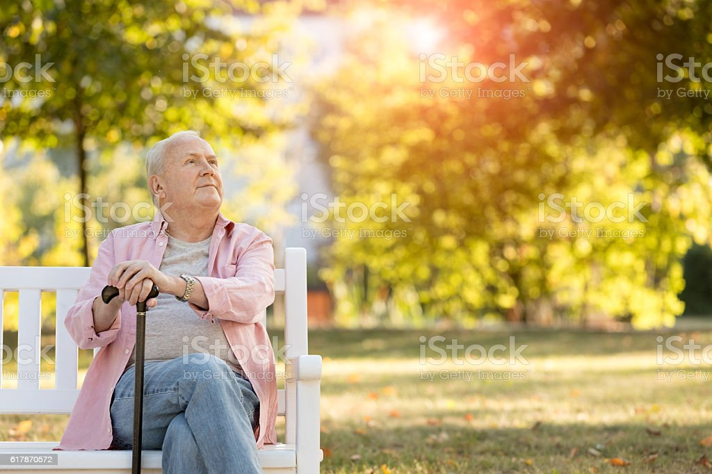 Senior man sitting on bench outdoors stock photo