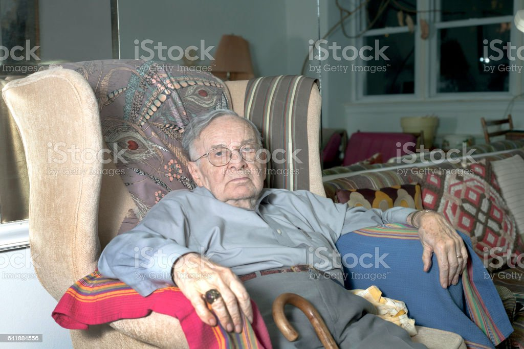 Senior man sitting on couch stock photo