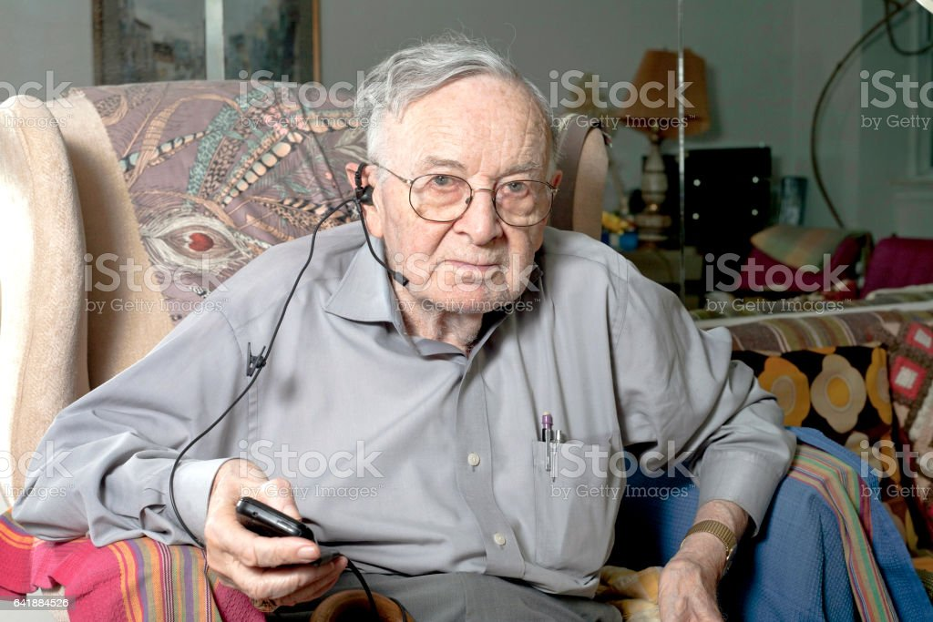 Senior man sitting on couch with headphone stock photo