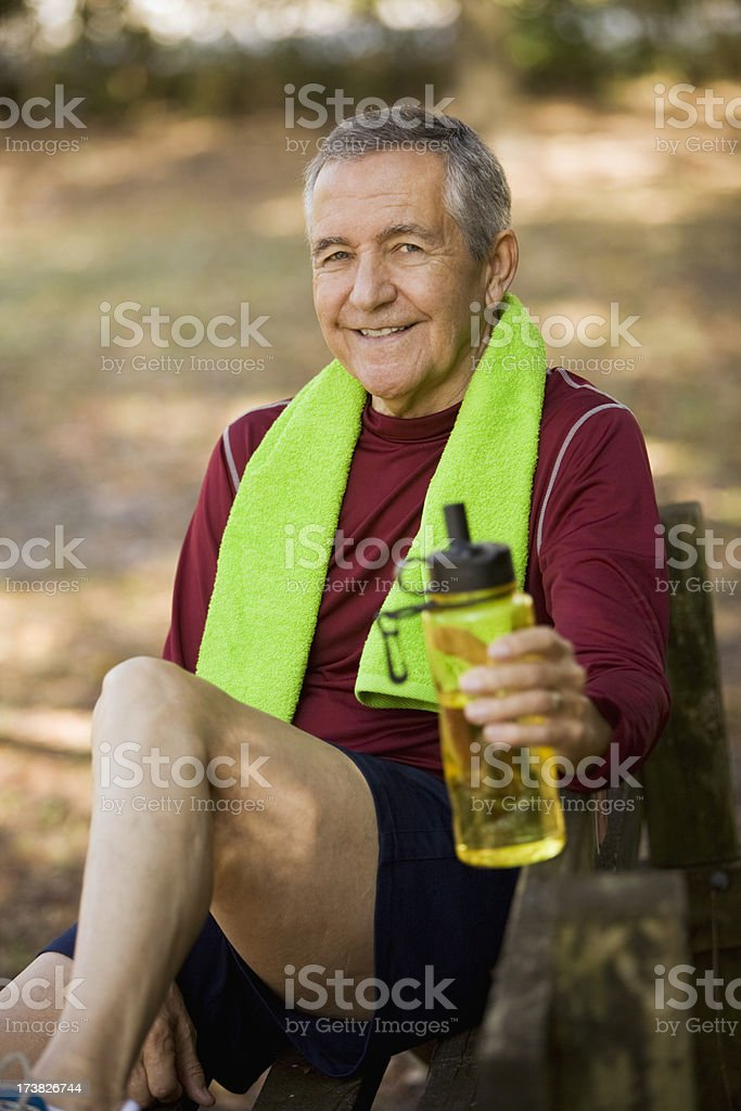 Senior man sitting on park bench holding water bottle royalty-free stock photo