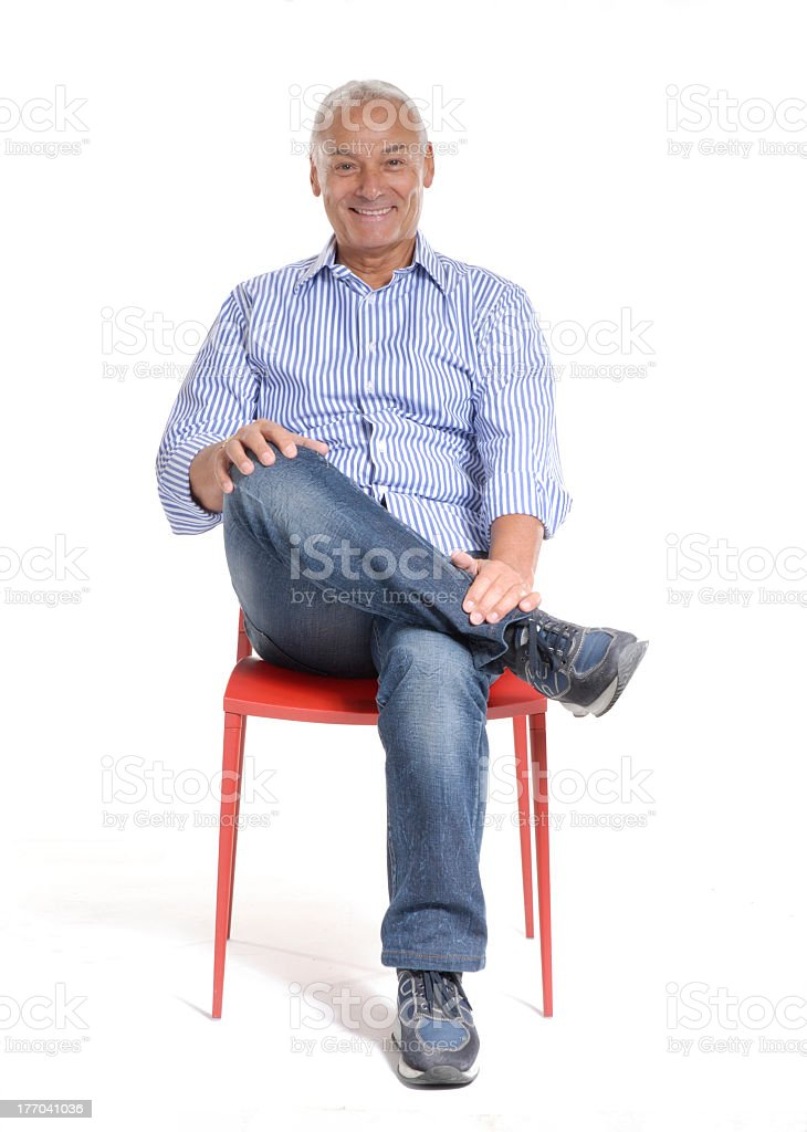 Senior man sitting on red chair with legs crossed royalty-free stock photo