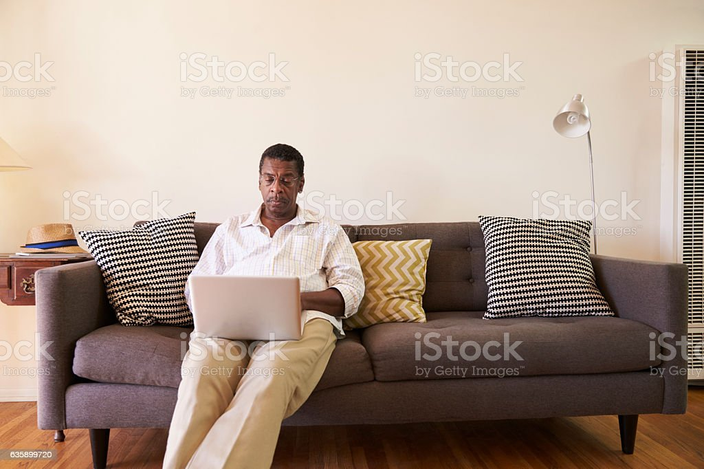 Senior Man Sitting On Sofa At Home Using Laptop stock photo