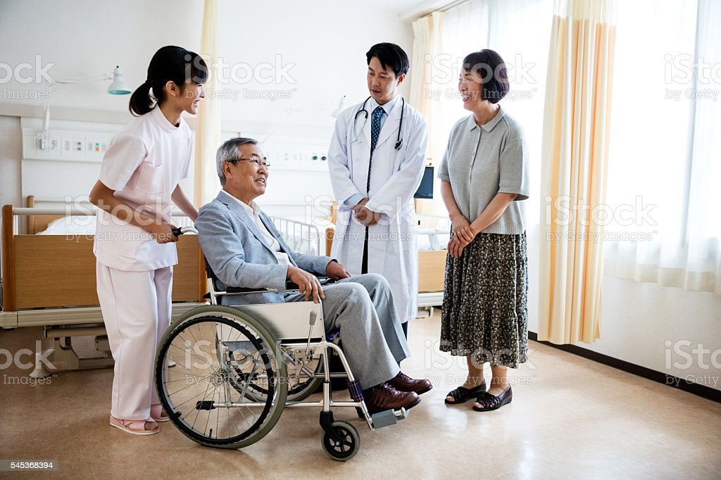 senior man sitting on wheelchair with doctor and woman standing stock photo