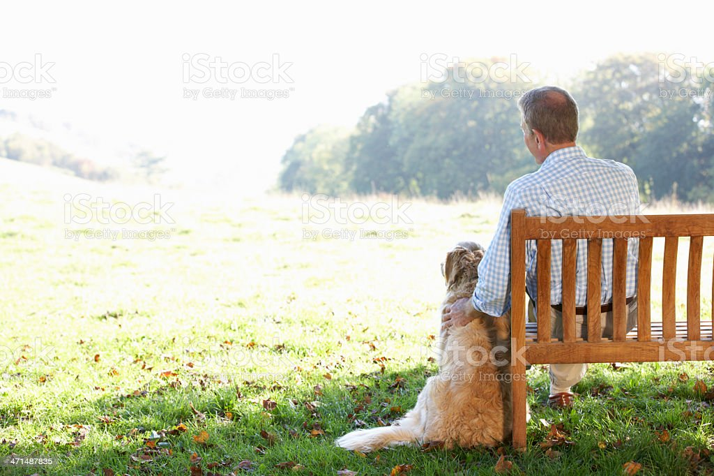 Senior man sitting outdoors with dog stock photo