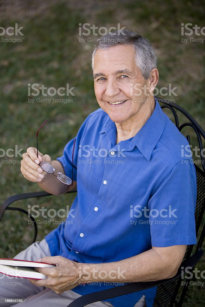 Senior man sitting outside holding a book and glasses royalty-free stock photo