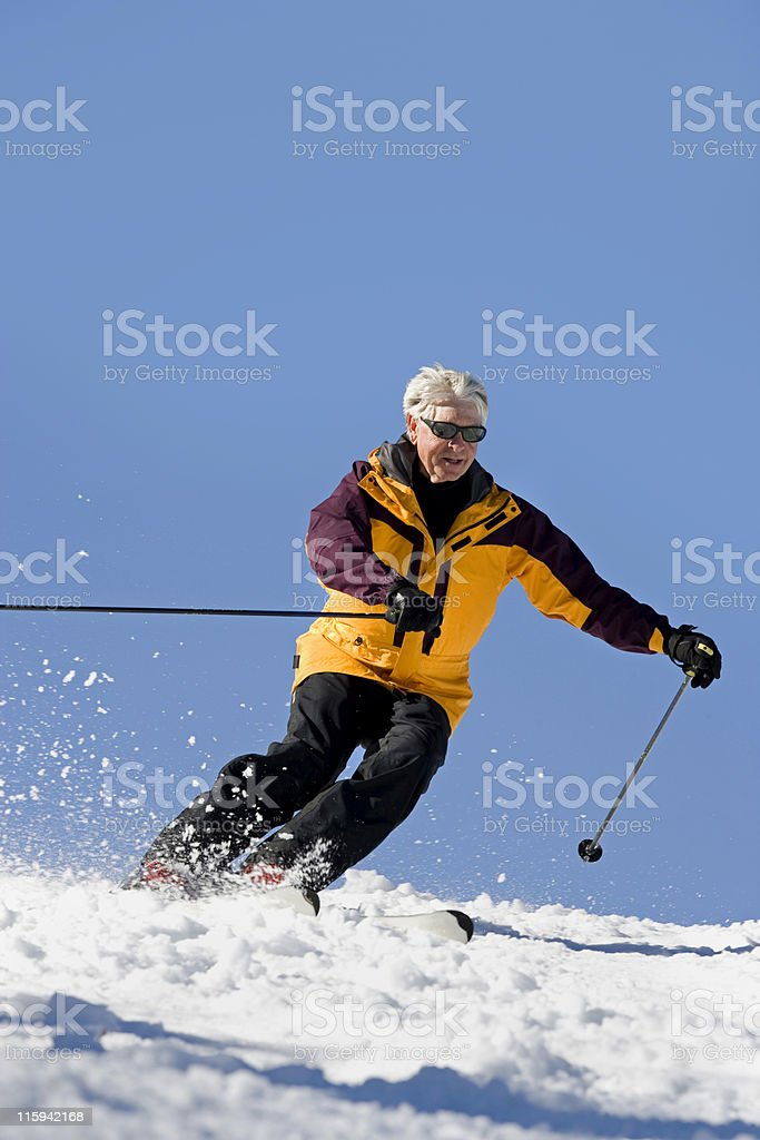 A senior man ski in the snow with a yellow jacket royalty-free stock photo