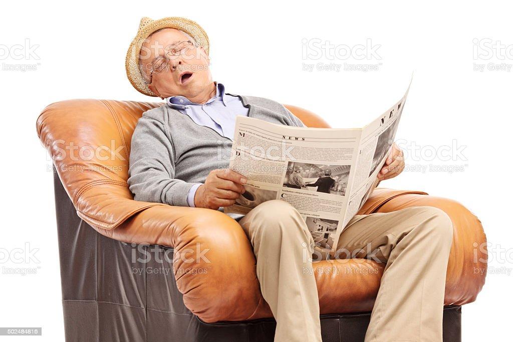 Senior man sleeping on an armchair stock photo