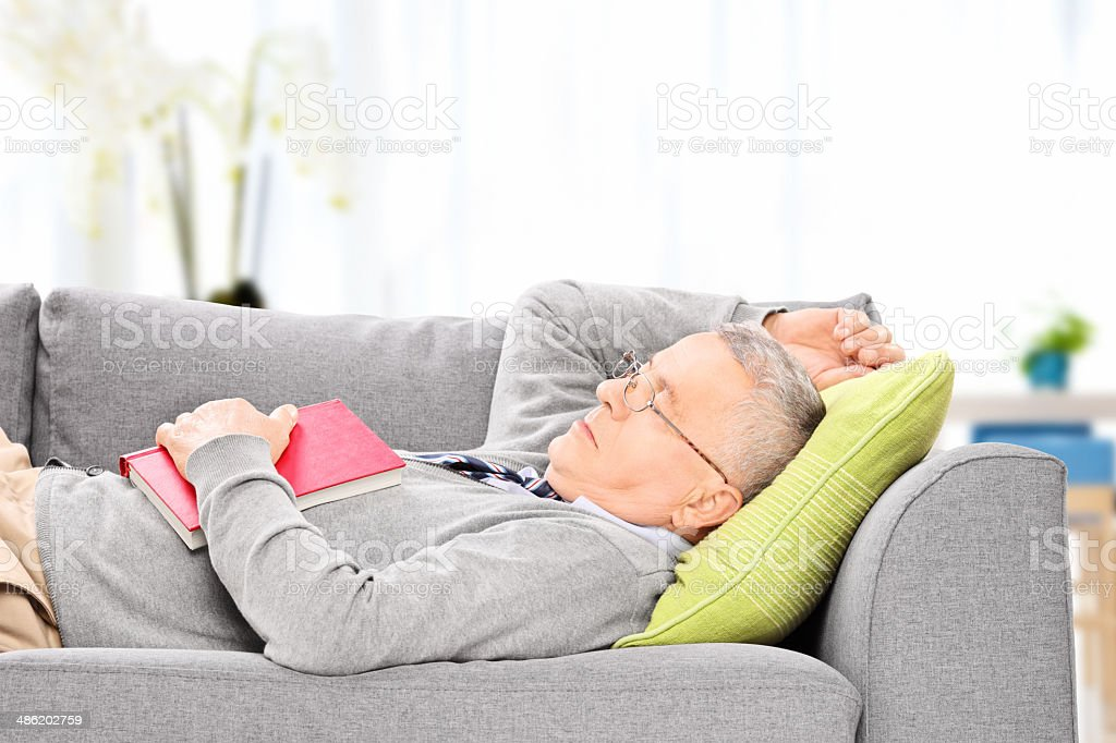 Senior man sleeping on sofa stock photo