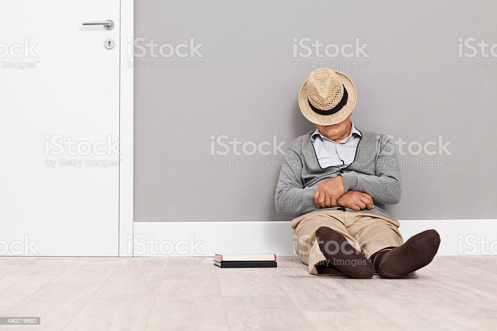 Senior man sleeping on the floor stock photo
